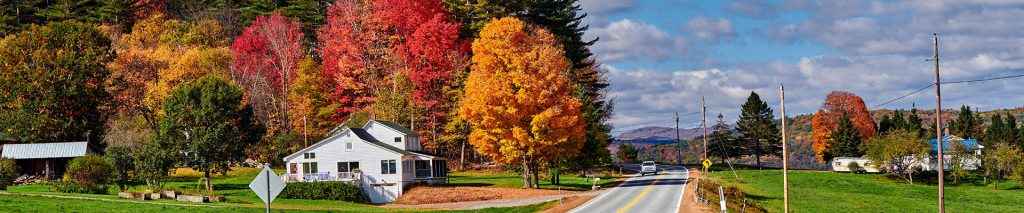 A country road winding by a white barn with bright autumn colored trees