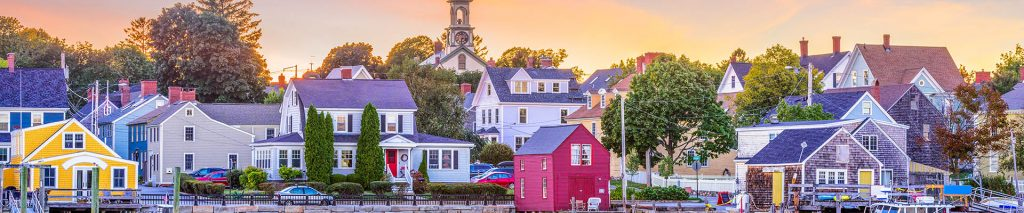 A small New England harbor town, viewed from the water at sunrise