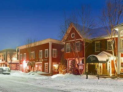 A snowy night with lights glowing in a small New England town