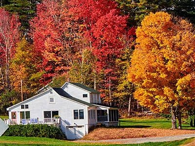 A New England farmhouse in front of colorful autumn trees